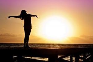 Femme qui profite du soleil sur un ponton au bord de la mer