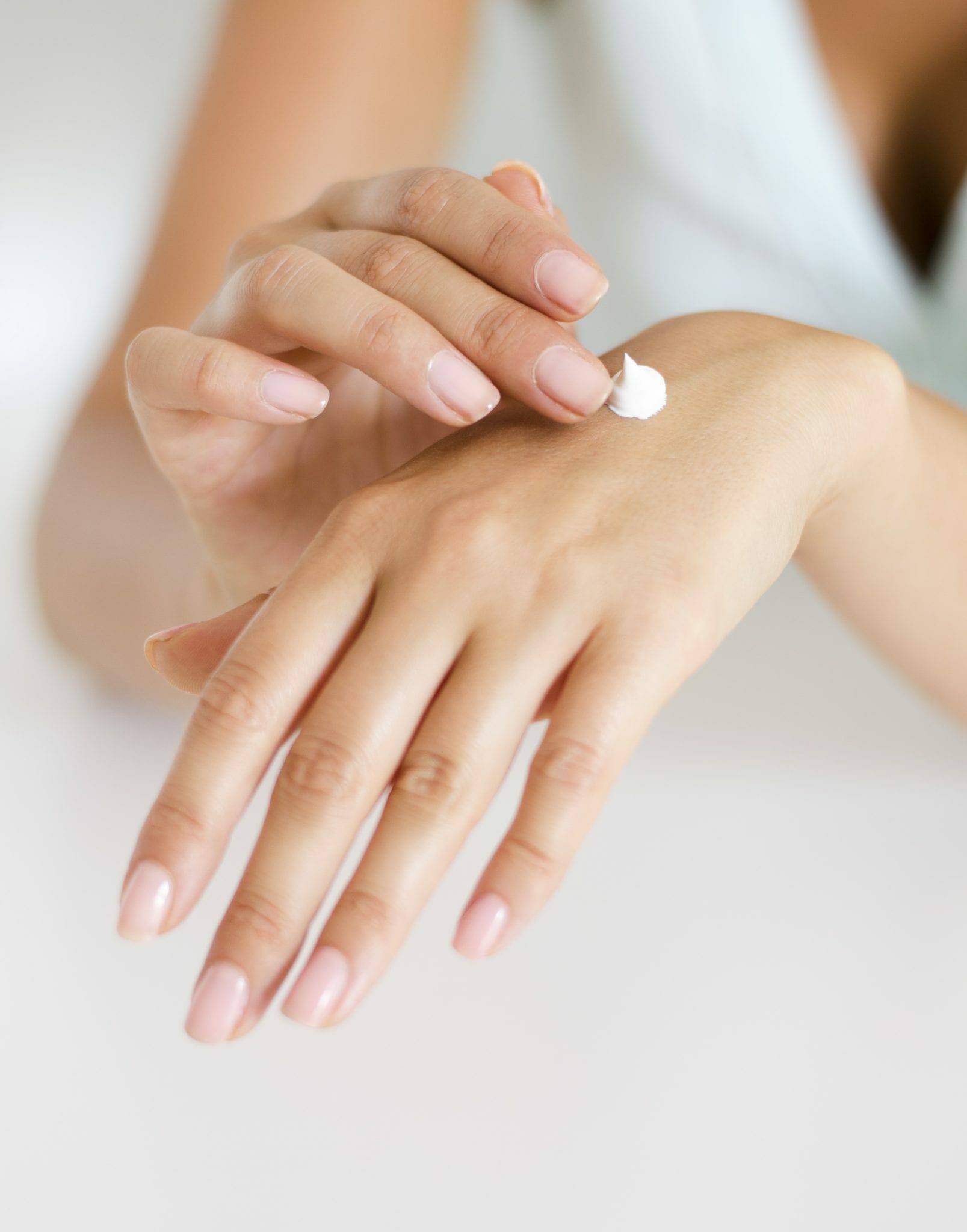 Une femme s'étale du lait sur la peau